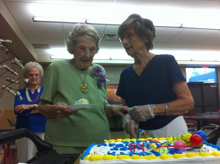 Elsie Pilcher and Virginia Morton cut her 100th birthday cake