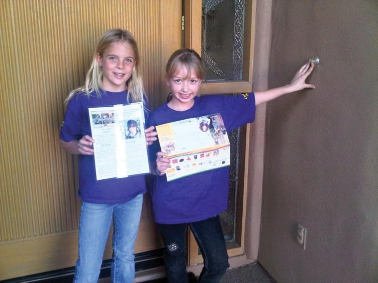 Morgan Foster (L) and Haidyn Moroz (R) selling Girl Scout cookie