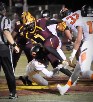 <p>Mountain Pointe's Rashie Hodge, Jr, (7) tries to run through a tackle by Corona's Brian McCluskey (13).</p>