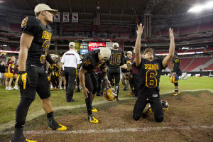 <p>Pride's Dominique Fenstermacher (6) throws grass in the air as Trey Lauer (3) and Wesley Payne (5) join him at the 50-yard line after winning the Division I football championship between Mountain Pointe Pride and Hamilton Huskies at University of Phoenix Stadium on Saturday, Nov. 30 2013.</p>