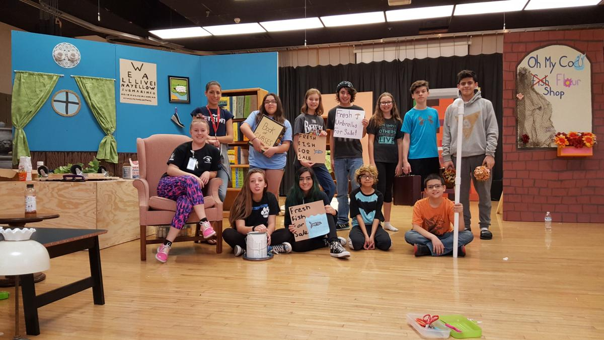Centennial Middle School teacher Kristi Mabee relaxes in a chair with the cast of her student play