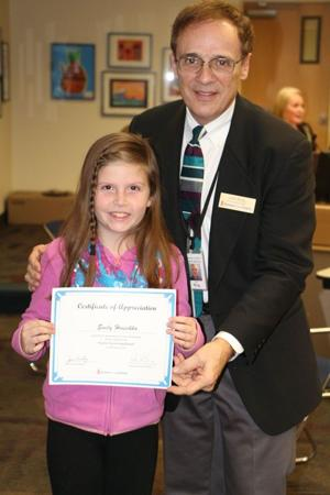 <p>He presents Sierra Elementary student Emily Hruschka with a citation. Instead of birthday presents, the 9-year-old girl told guests at her party to bring donations for the Kyrene Foundation Resource Center for needy kids.</p>