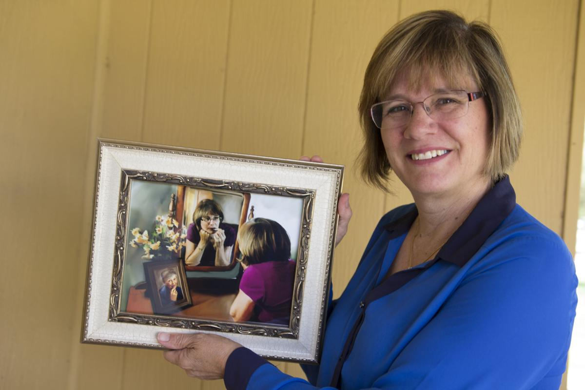 Author Lynne Hartke holds a gift made by her daughter – a digital portrait of Hartke applying lipstick near a portrait of her mom doing the same.
