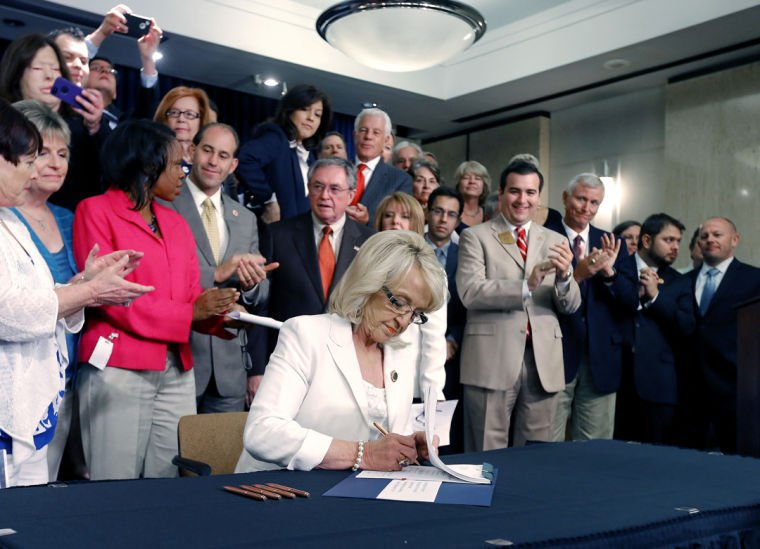 Jan Brewer signs Medicaid expansion law