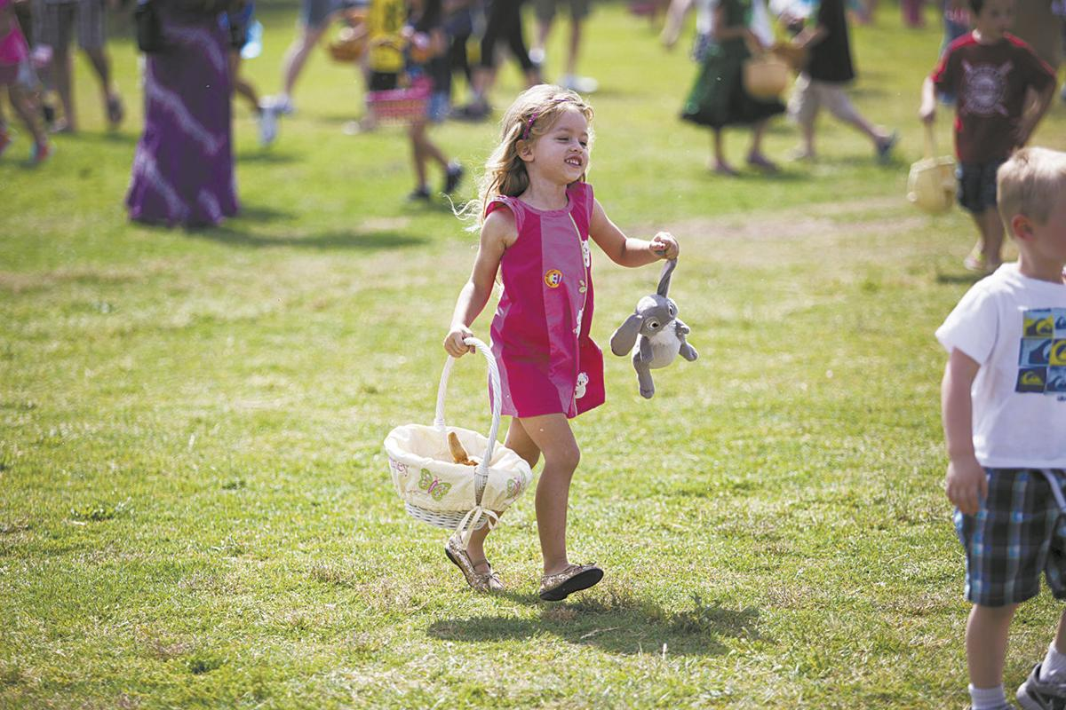 A young girl enjoys the day hunting for eggs at Snedigar Sportsplex's free Family Easter Celebration