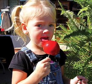 <p>Emma Caldwell of Tennessee, grandaughter of Rev. and Mrs. Charles Thomas, enjoys a candied apple. Rev. Thomas is pastor of the Congregational Methodist Church.</p>
