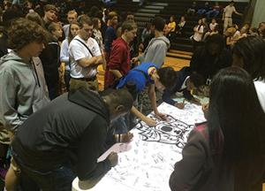 "<p>Lincoln High School students sign a banner during the ""Students Affecting Lives Everyday"" anti-bullying rally held at the school's gymnasium Friday. Each signature represented a pledge by the students to positively affect at least one student's life every day.</p>"