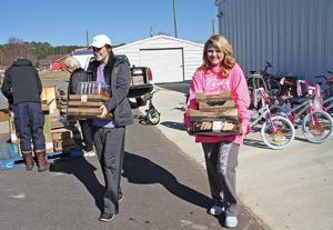 <p>Macy Bridges (left) and Darby Bryant carry food to be loaded on trucks.</p>