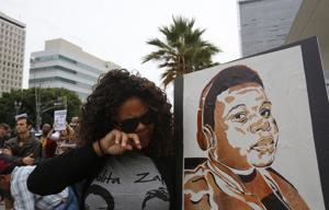<p>Melissa Duprey, cries while holding a poster of Michael Brown during a protest in front of the LAPD headquarters, during a protest in Los Angeles on Friday, Dec. 5, 2014, in response to the Eric Garner chokehold decision in New York. (Gary Friedman/Los Angeles Times/TNS)</p>