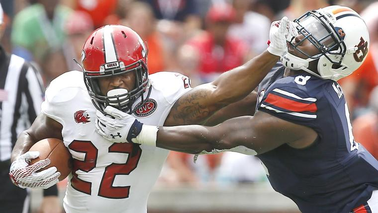 Jacksonville State running back Josh Clemons stiff arms Auburn linebacker Cassanova McKinzy during the JSU at Auburn football game. Photo by Stephen Gross / The Anniston Star