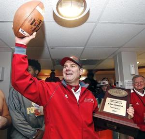 <p>Jacksonville State head coach John Grass holds the game ball and the OVC Championship trophy after the Eastern Illinois at Jacksonville State football game.</p>