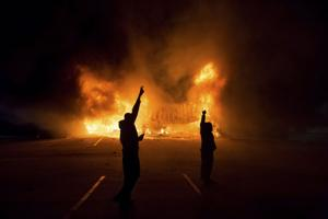<p>People stand near a burning AutoZone store on West Florissant Avenue following the St. Louis County grand jury decision in Ferguson, Mo., in the early morning hours Tuesday. (Whitney Curtis/The New York Times)</p>