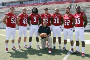 <p>Jacksonville State head coach John Grass poses with players that have already graduated during picture day Friday morning at Burgess-Snow Field at JSU Stadium. They are from left: Andrew Dean, Ben Endress, Omari Jones, Max Holcombe, Nigel Terrell, Chad Sharp and Jeremy Harrison.</p>