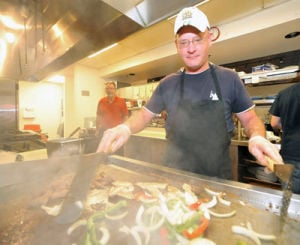 <p>Duffy Dempsey, kitchen manager at Red Pepper Grill in Oxford, works through the steam on a patron's order. (Anniston Star photo by Bill Wilson)</p>