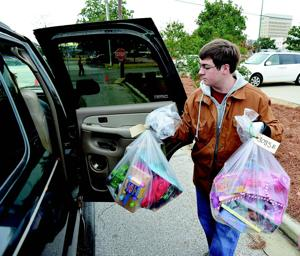 <p>Jake Bolton loads some of the toys for delivery Thursday.</p>