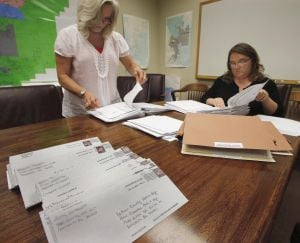 <p>Absentee ballot clerks Diane Harden, left, and Shasta Platt go through some of the 364 absentee ballots that came into their office for the District 1 Calhoun County Commission race between James Montgomery and Fred Wilson. (Editor's note: The top image has been manipulated to obscure voters' addresses.)</p>