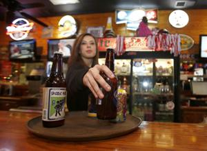 <p>Susan Grace Catrett puts beer on her serving tray at Struts in Jacksonville. The city of Jacksonville is considering loosening some of its restrictions on alcohol sales.</p>