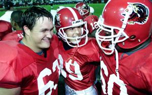 <p>Ashley Martin (center) is congratulated by teammates Trace Newton (left) and Deon White after making her record-setting kick against Cumberland in 2001. Photo by Trent Penny/The Anniston Star</p>
