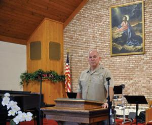 <p>THE REV. Mark Kincaid poses at the pulpit of Owosso Free Methodist Church Tuesday. Kincaid is leaving the church June 5 after 15 years of leadership.</p>