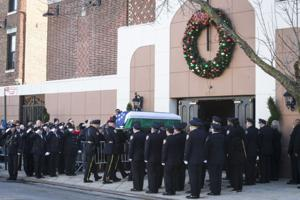 Fellow New York City police officers salute fallen comrade