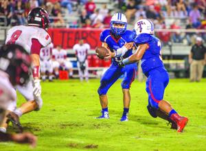 <p>Tidehaven sophomore Jeff Williams (3) takes a handoff from sophomore quarterback Bryce Galvan (11) as Palacios' Sam Schulman (8) moves in. Williams picked up 87 yards and two touchdowns on 12 carries against Palacios Friday night at Delvin Taska Stadium in El Maton. The Tigers defeated the Sharks 43-0.</p>