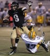 West's Ty Webb, 9, is tackled CMR's Bryan Evans, 73 and Jake Horton, 13