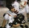 Senior's Luke Paine, 11, is tackled by West's Jake Leinwand, 53,