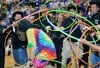 Special Olympic athletes throw hula-hoops over a buffalo costume