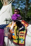 A young girl rides in the Saturday morning Crow Fair Parade