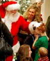 Children and their parents rush to greet Santa
