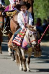 A young boy rides in the Saturday morning Crow Fair Parade