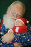Santa cradles a sleeping baby