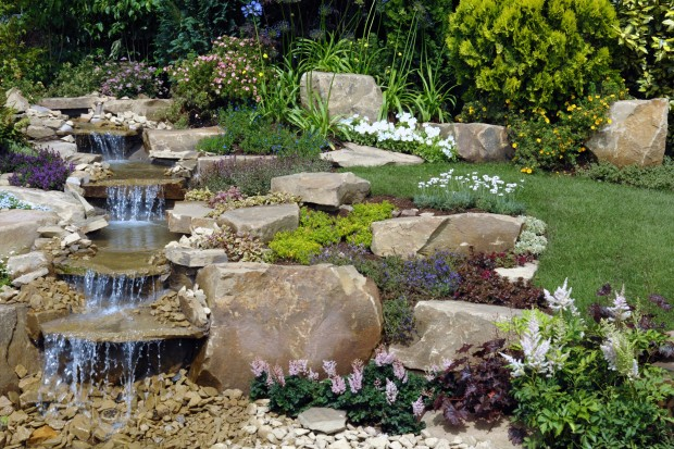 Pondless water features infuse your home with soothing for Pictures of backyard waterfalls