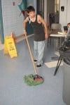 Cody Younghawk mops the floor at the emergency shelter