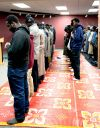 Muslim men line up in prayer a