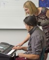 Lame Deer music teacher Natalie Parker helps Micheal Bowers on the keyboard