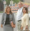 Attorney Cammi Woodward, left, and Myong Suk McFarland and Gregory L McFarland leave court