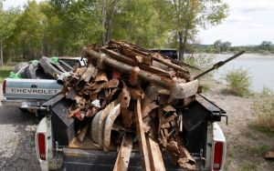 Trucks are loaded with rusty metal, tires, and other debris