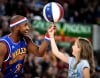 Globetrotter Dizzy Grant teaches a fan to spin a basketball