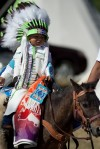 A child rides in the Saturday morning Crow Fair Parade
