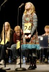 Fifth-grader Cailin Fiddler cranes to reach the microphone