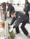 Vince Francischetti puts a Christmas wreath on a grave