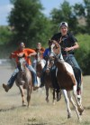 Kids on horse back race through the Crow Fair grounds