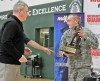 Montana National Guard Colonel Arnold Marquart hands the MaxPreps Tour of Champions Trophy to Billings Central Rams Football Coach Jim Stanton