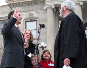 Montana Supreme Court Chief Justice Mike McGrath, right, swears in Gov. Steve Bullock as Bullock's family looks on, Monday, Jan. 7, 2013, in Helena, Mont. Bullock's inauguration was followed by the opening of the 2013 legislative session. (AP Photo/Matt Volz)