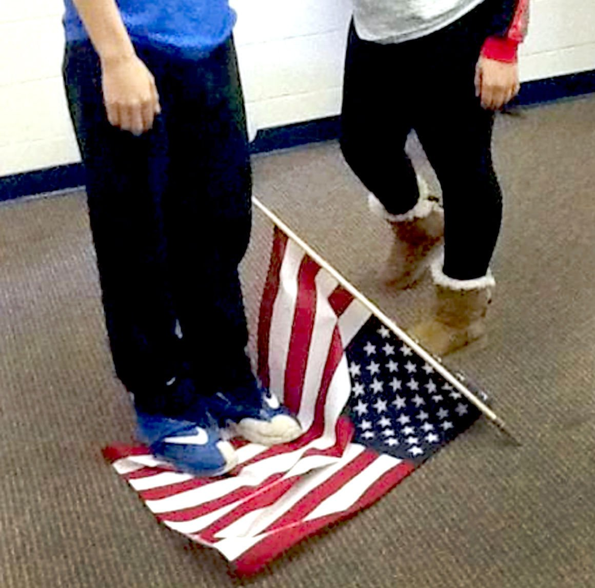 Photo Of Teen Standing On American Flag Prompts School