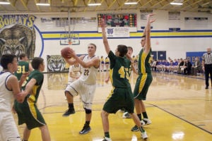 <p>Senior Ben Twedt (22) uses his athleticism to get the shot up over the Beckman Catholic defenders.</p>