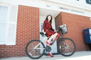 <p>Waverly Newspapers' own Meredith Toey poses in high heels on a bicycle just outside of where all the magic that put this paper together happens.</p>