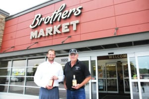 <p>Jared DeVries, owner of Brothers Market, with brothers Jay and Darin, and Keith Kerkhoff, owner Templeton Rye, pose outside Denver's new grocery store.</p>