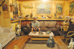 <p>Terry Dengler in his sanctuary of wood carvings, a hobby and business he now calls Chainsaw Creations.</p>